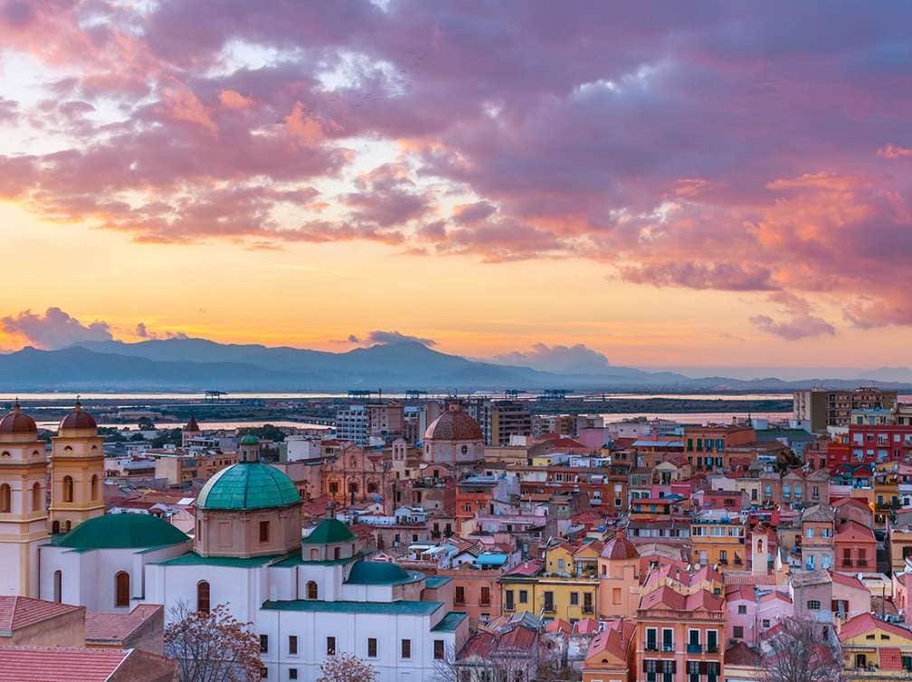 Sunset on Cagliari, evening panorama of the old city center in Sardinia Capital, view on The Old Cathedral and colored houses in traditional style, Italy